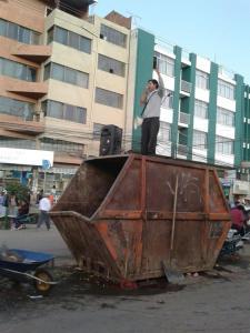 Pregando sobre latão de lixo na cidade de Cochabamba